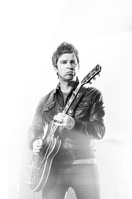 Noel Gallagher plays guitar on stage