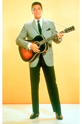 Elvis Presley plays guitar in suit