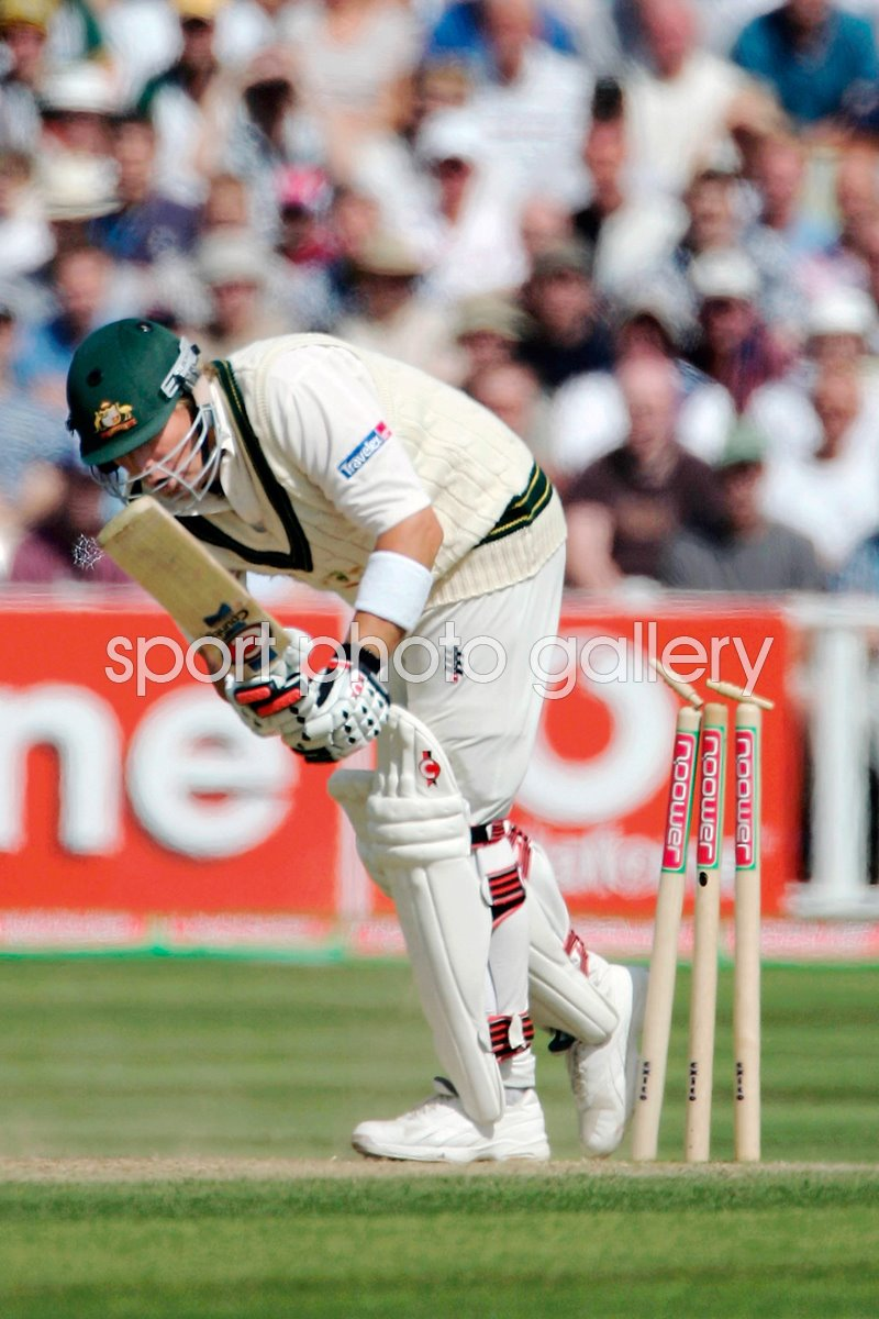 Shane Warne steps onto his stumps