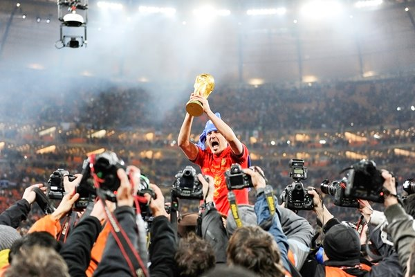 David Villa with the trophy surrounded by paparazzi