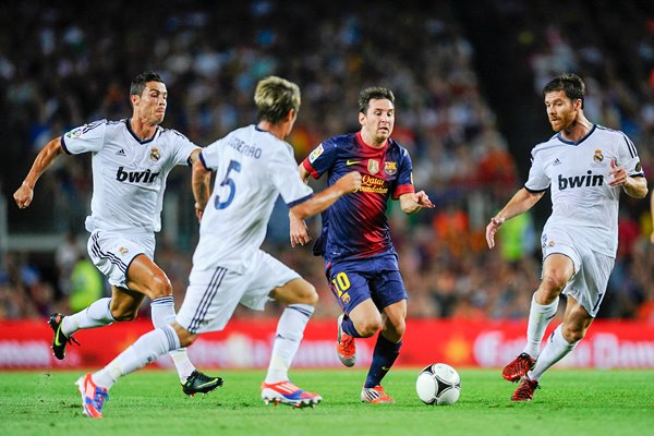Leo Messi of Barcelona duels for the ball v Real