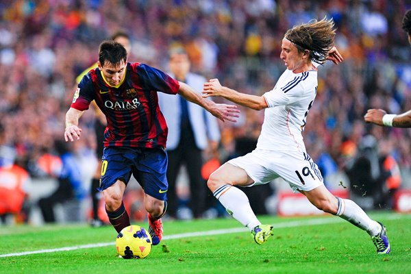 Lionel Messi duels for the ball with Luka Modric