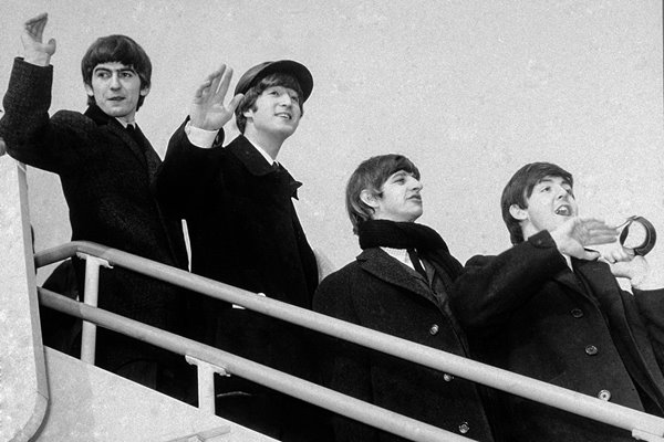 The Beatles wave from airplane steps