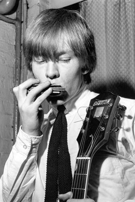 Brian Jones of Rolling Stones playing a harmonica