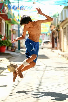 A young boy plays football on the streets of Manaus